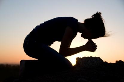 Mulher rezando de joelhos