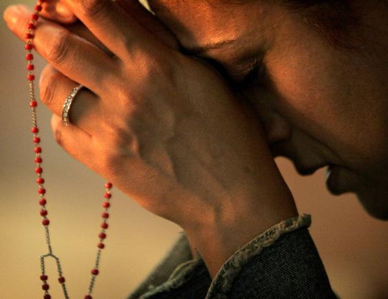 Mulher rezando o terço vermelho