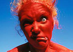 nude_woman_wearing_red_body_paint_making_face_outdoors_700-00054203
