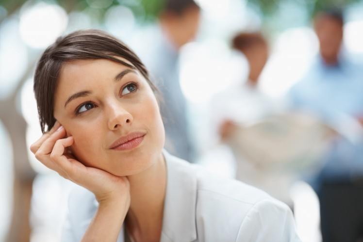 Cute young thoughtful business woman looking away