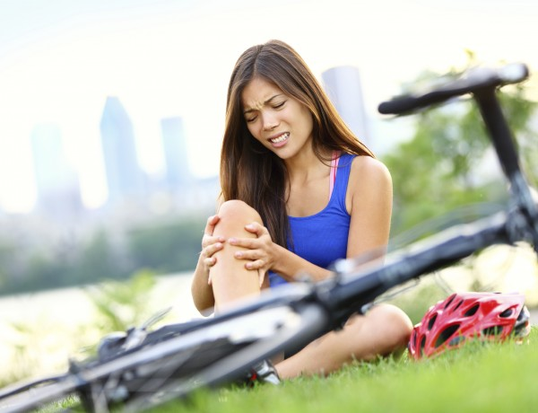 Knee pain bike injury. Woman with pain in knee joints after biking on bicycle. Girl sitting down with painful face expression. Mixed race sport fitness model outdoors.