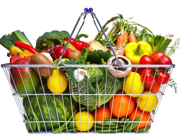 Photo of a wire shopping basket full of fresh fruit and vegetables, isolated on a white background.