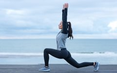 Beautiful brunette woman stretching on a seafront wearing sports clothes as a warming up exercise