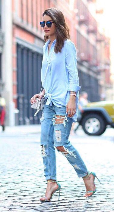 Camisa mais larguinha com nó e jeans destroyed. O toque mais arrumado fica por conta da bolsa pequena e do scarpin