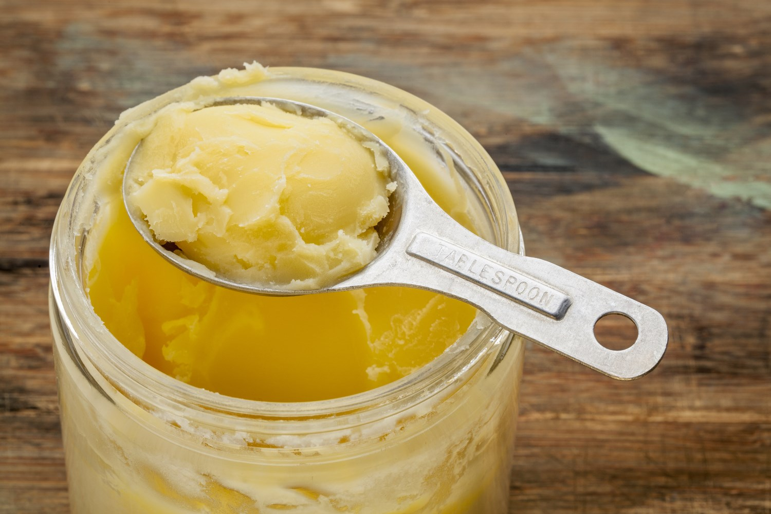 jar and measuring tablespoon of ghee - clarified butter
