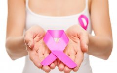 Woman holding a pink cancer awareness ribbon in her hands