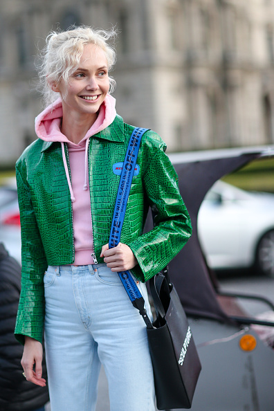 PARIS, FRANCE - MARCH 07: Olga Karput wears a pink hoodie sweater, a green jacket, jeans pants, a black bag, and black boots, outside the Louis Vuitton show, during Paris Fashion Week Womenswear Fall/Winter 2017/2018, on March 7, 2017 in Paris, France. (Photo by Edward Berthelot/Getty Images)