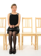 Anxious young lady sitting on a chair and waiting.