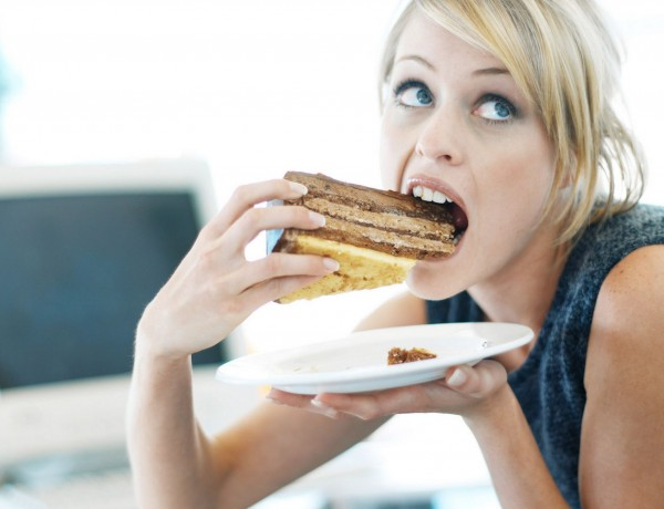 woman-eating-a-large-piece-of-cake