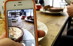 Two people photographing their food in a café with their smartphones.