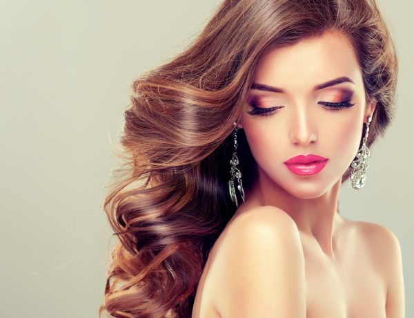 Beautiful model brunette with long curled hair and jewelry earrings