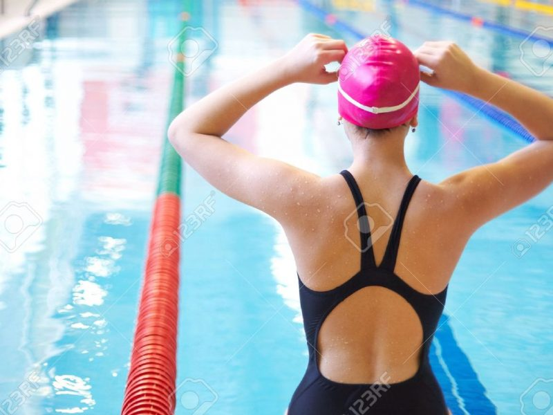 12467088-young-woman-wears-glasses-in-front-of-the-swimming-pool-back-stock-photo