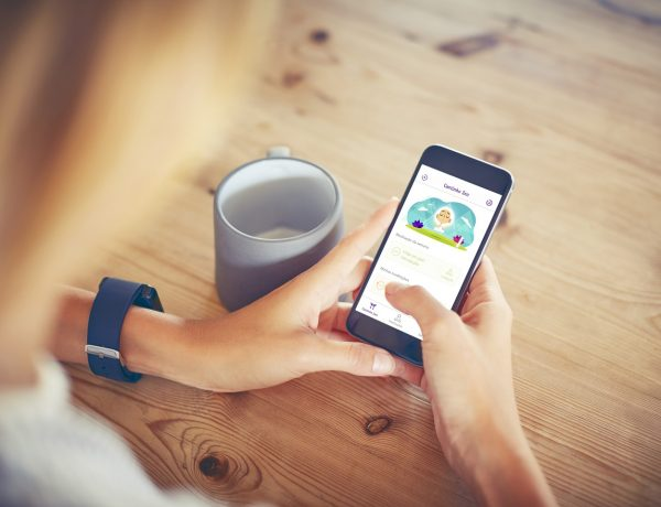 Over the shoulder view of woman using smart phone. Female is holding mobile phone with blank screen. Coffee cup is kept on wooden table.