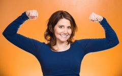 Closeup portrait beautiful, pretty model woman flexing muscles showing, displaying her strength, isolated orange background. Positive human emotions, facial expressions, feelings, attitude, perception