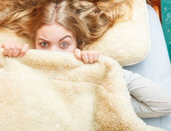 Woman waking up in bed in the morning after sleeping. Well rested young girl laying covering face with wool woolen blanket.